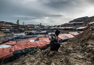 A woman carries a jar of water up a muddy slope in Balukhali camp, where thousands of Rohingyas are now living. photo: Tommy Trenchard/Panos