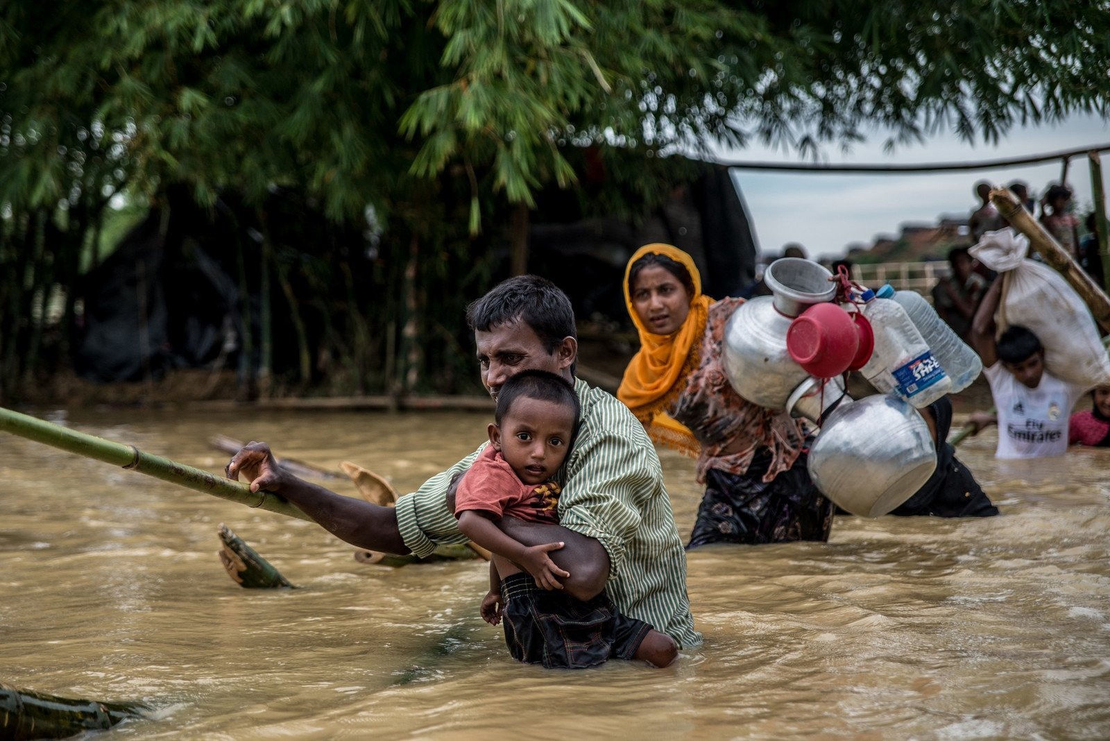 A father carries his son across a broken bamboo bridge on the edge of Balukhali camp, Bangladesh. Three days of heavy rains flooded many of the areas where people had set up temporary shelters, forcing them to move to higher ground. photo: Aurélie Marrier d'Unienville