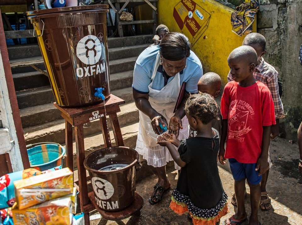 Photo: Tommy Trenchard / Oxfam Community health worker Marrion Thomson teaches children how to wash their hands at an Oxfam Hand Washing Point in Congo Town, an area in Freetown, Sierra Leone.