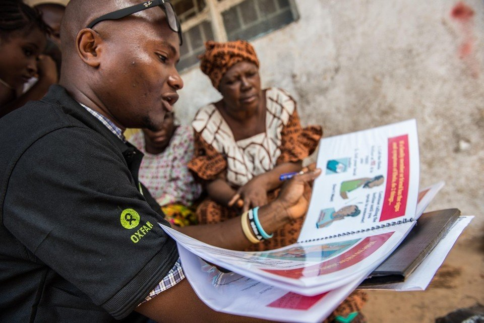 Photo: Tommy Trenchard / Oxfam Abdul Razak Baimba, A Community Health Worker talks with residents of Congo Town in Freetown (Sierra Leone) about Ebola. Oxfam has provided handwashing stands in the area and have also trained Community Health Worker teams who teach the community about the signs and symptoms of Ebola, how to prevent it and what to do if a family member becomes infected.
