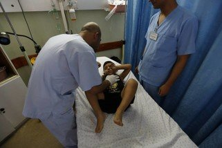 Doctors at the Oxfam-supported Al Awda Hospital in northern Gaza treat a young boy.