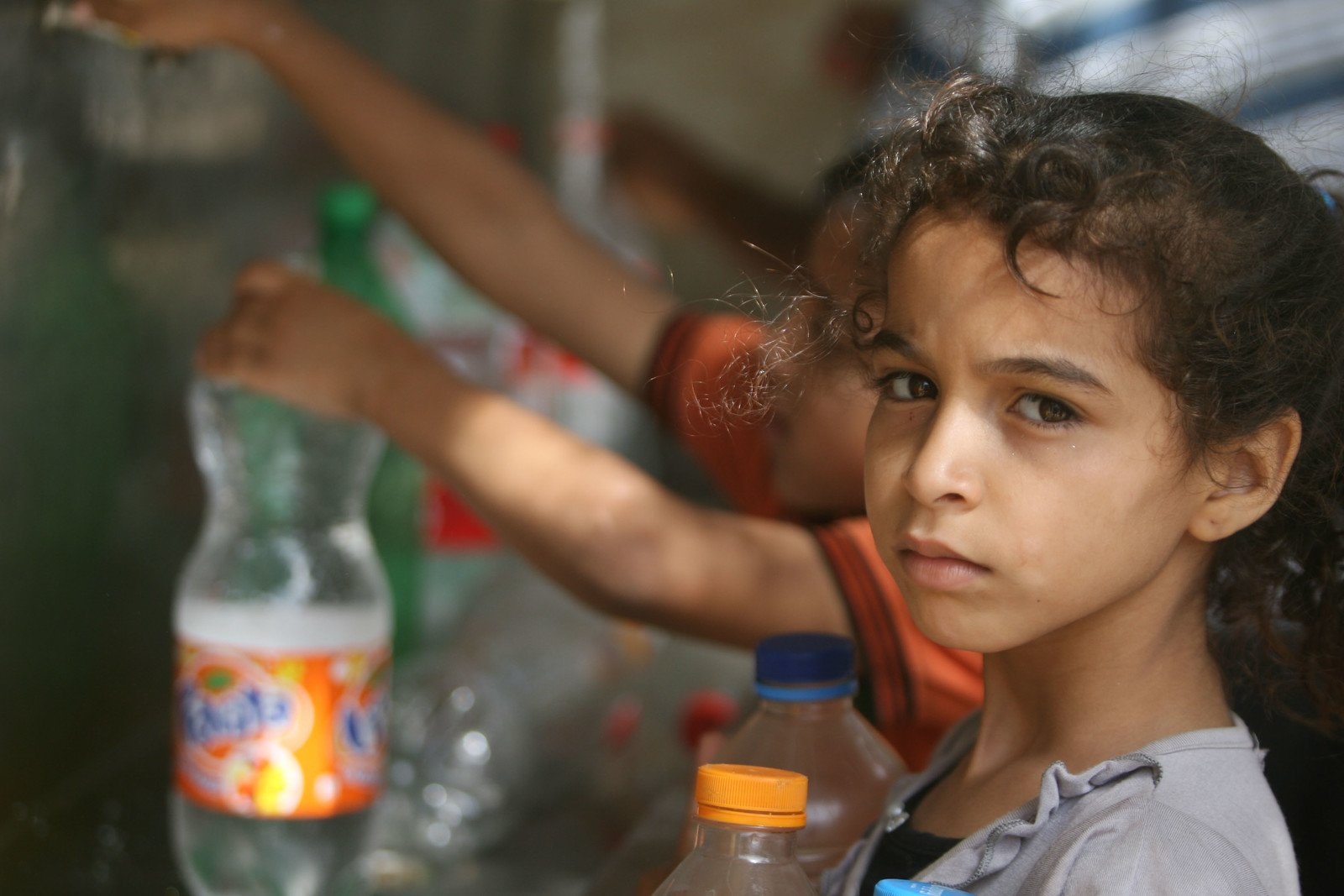 Children in Rafah, southern Gaza, collect water from one of the working public taps. Numerous water systems and wells have been badly damaged in the airstrikes.