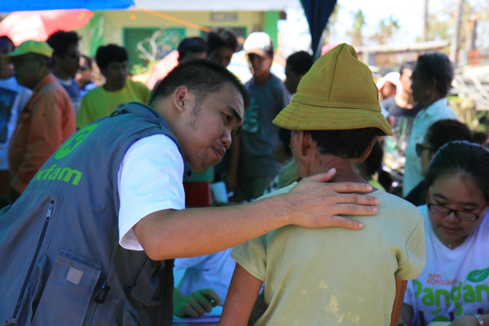 Oxfam staff Vincent Malasador gives support and reassurance to recipient during the distribution of hygiene items in northern Cebu.