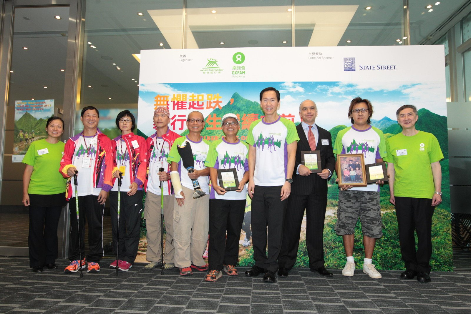 (From left to right) Kanie Siu (Director of Fundraising & Communications, Oxfam Hong Kong); Kim Mok (visually-impaired trailwalker); Alsa Kwok (visually-impaired trailwalker); Michael Ng (hearing-impaired trailwalker), amputee trailwalker Fung Kam Hung; Mrs Fung; Bernard Chan, Francesco M. Squillacioti from State Street; Tse Chi Kin; Stephen Fisher (Director General, Oxfam Hong Kong) gathered for a group photo.