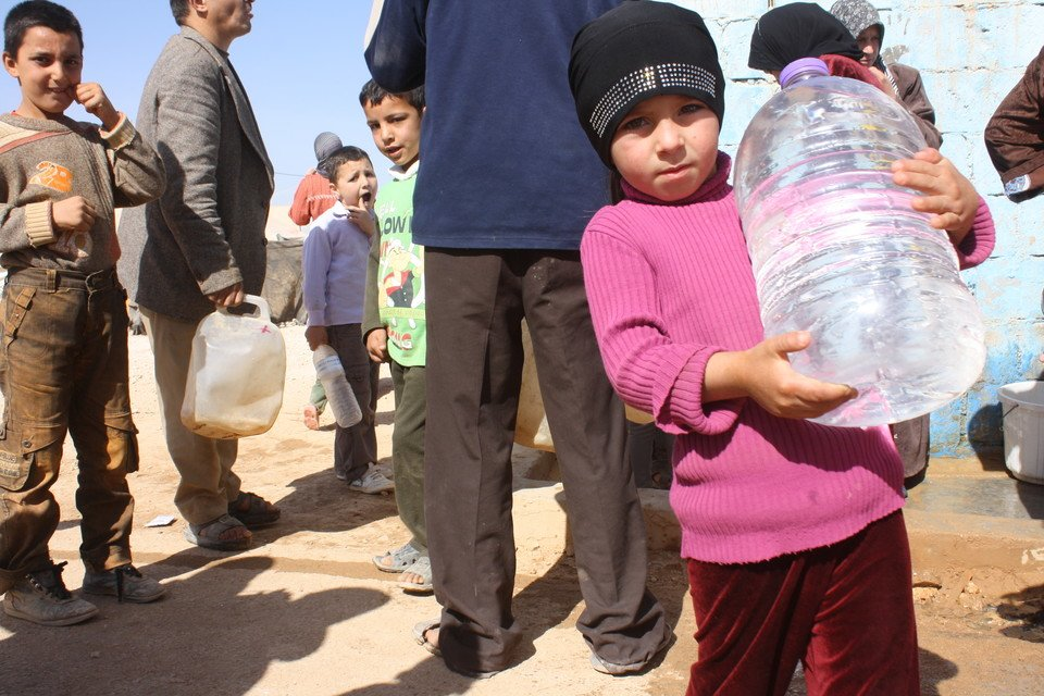 Refugees collecting water that has just been delivered to the Zaatari