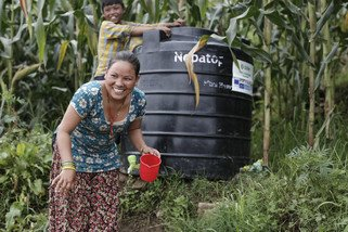 Sushila and Deepak collect clean water from an Oxfam tank. The tank supplies ten households in the village of Burunchili, where only 25 of its 200 houses were left standing. Oxfam supplied the village with clean water, toilets and hygiene kits. (Photo: Sam Tarling/Oxfam)