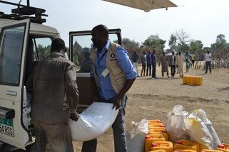 Oxfam staff unload food aid, including beans and oil at the Nyal airstrip. (Photo: Corrie Sissons/Oxfam)