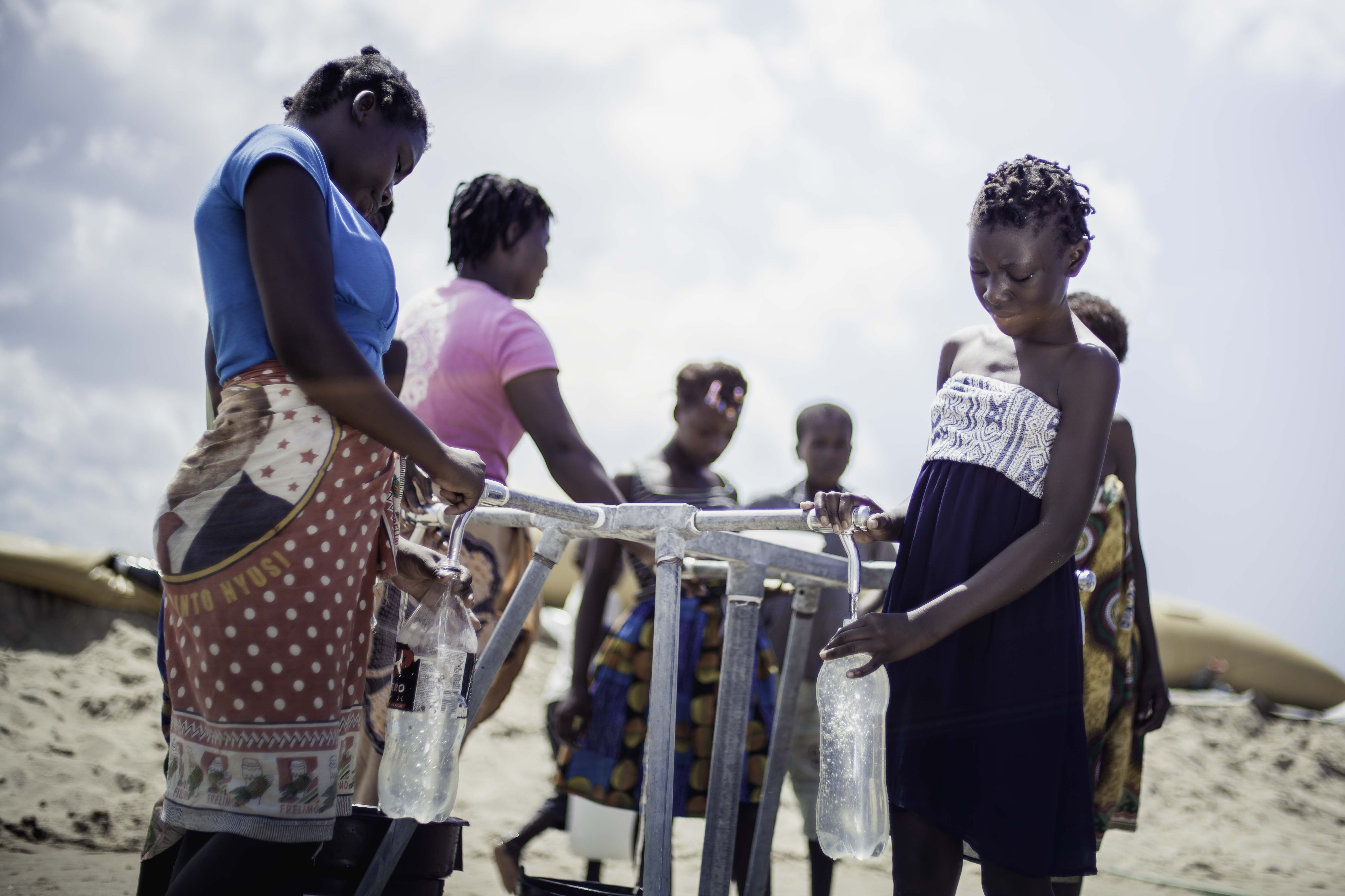 Teresa Jone Vilanculos (right), 14, filling her bottle at the tap stand. She has fled her village Mangalaforte, together with her family, when their house was washed away in cyclone Idai. (Photo: Micas Mondlane / Oxfam Novib)