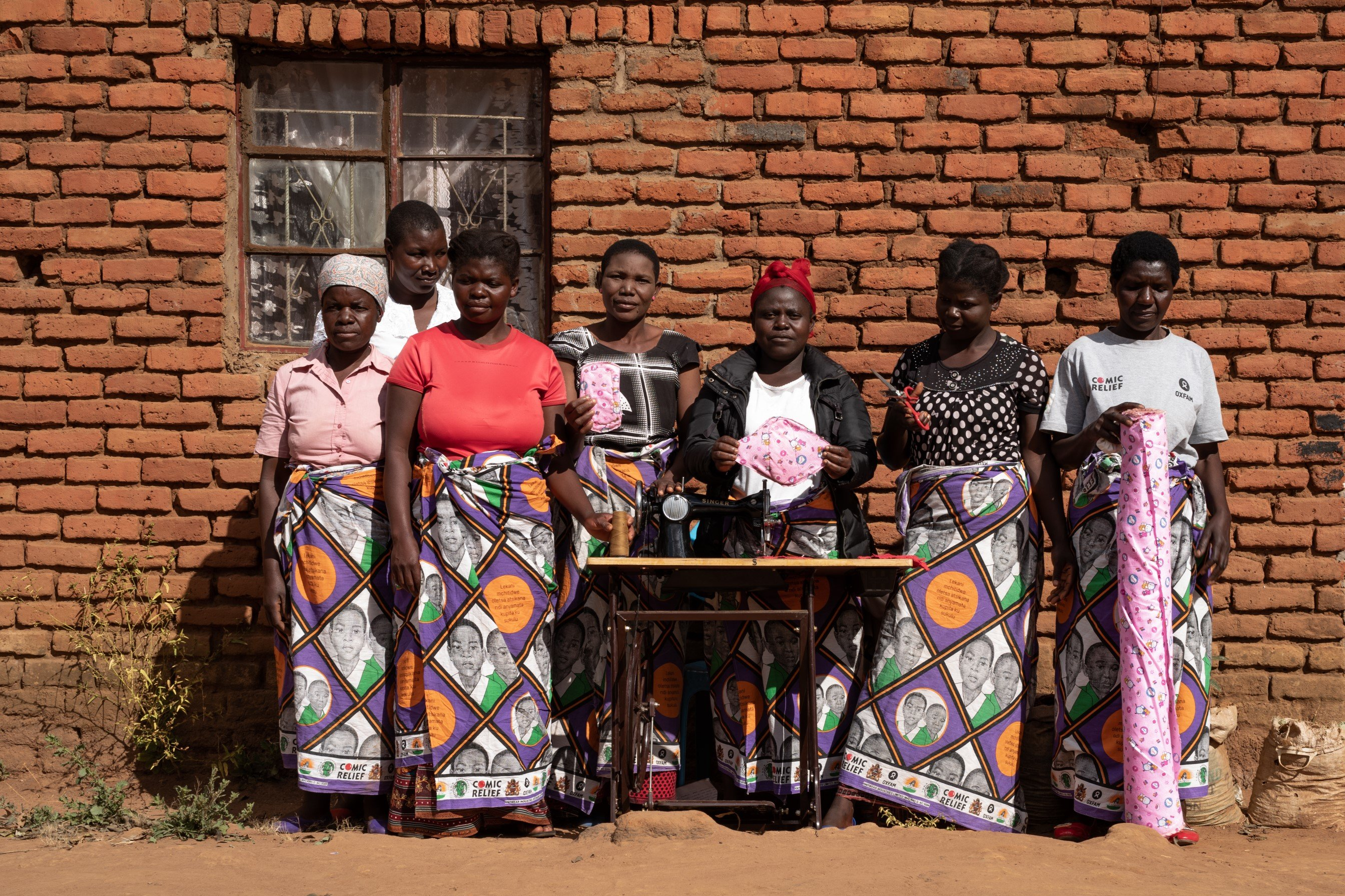 The mothers' group with a sewing machine and reusable sanitary napkin they made.