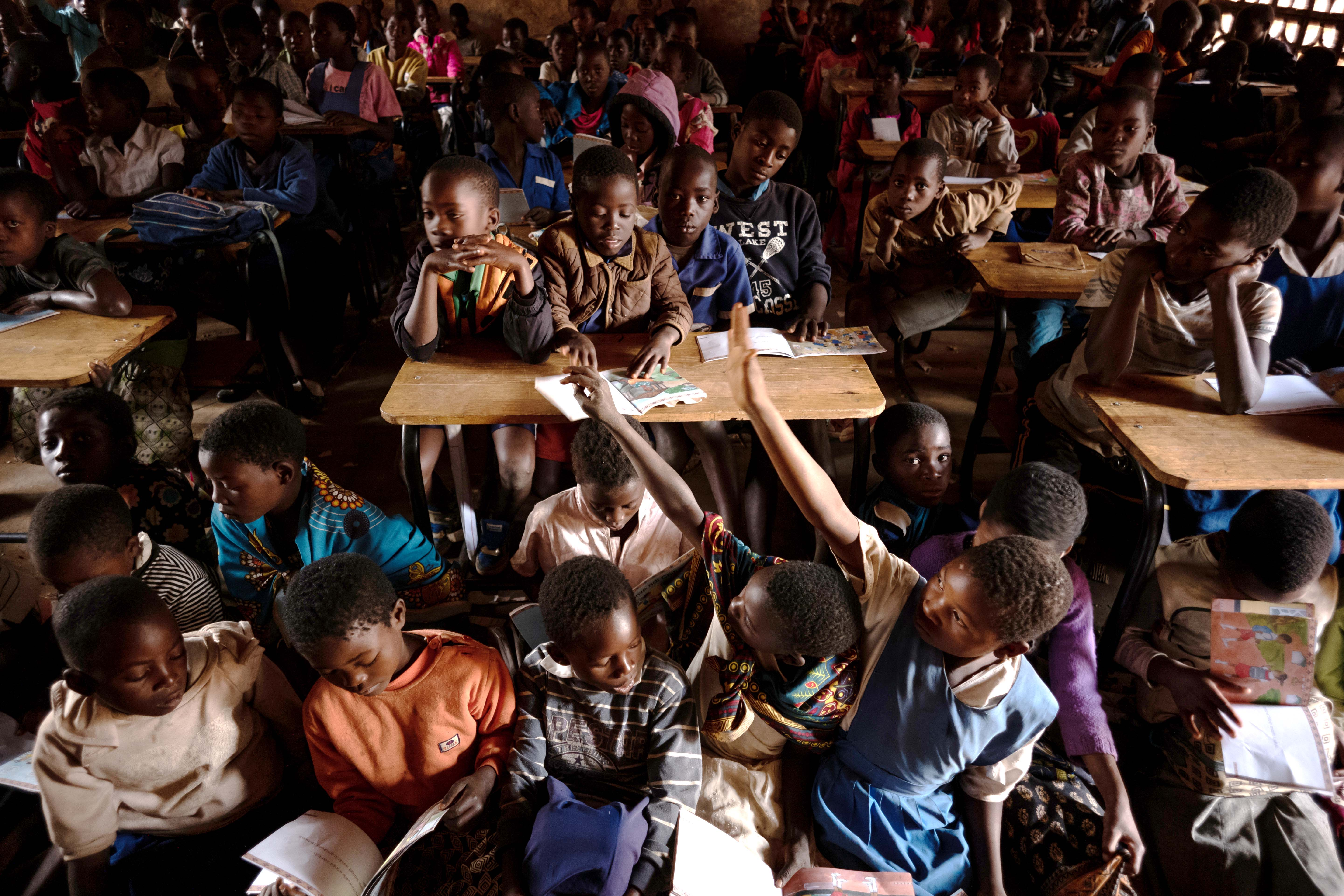 Despite sitting in a packed and dimly lit classroom, students are eager to learn because many of them have been out of school.