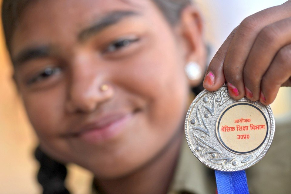 Komal, a young girl, holding up a medal she received.