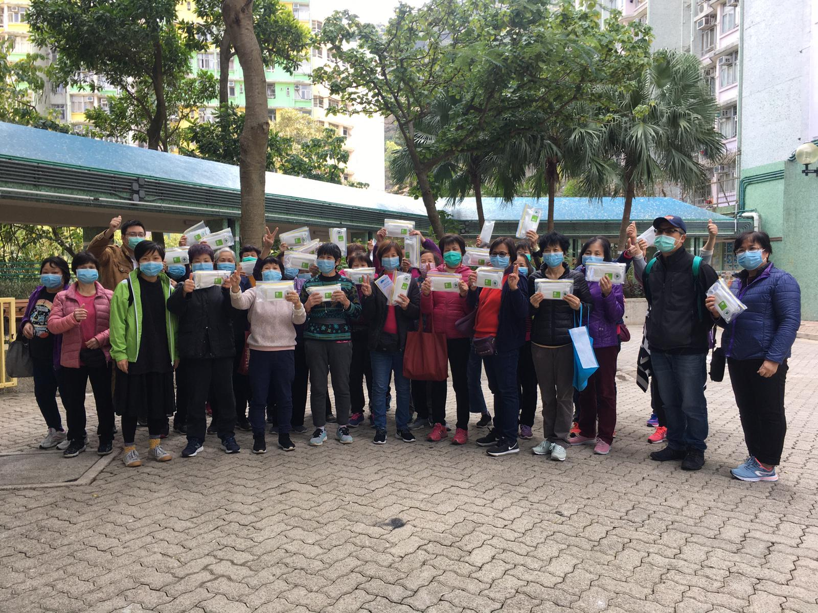 Cleaners at Yiu Tung Estate, Shau Kei Wan, holding the masks they received.